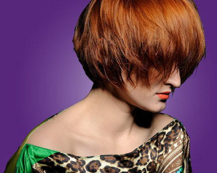 Red headed woman with short, angled hair styling
